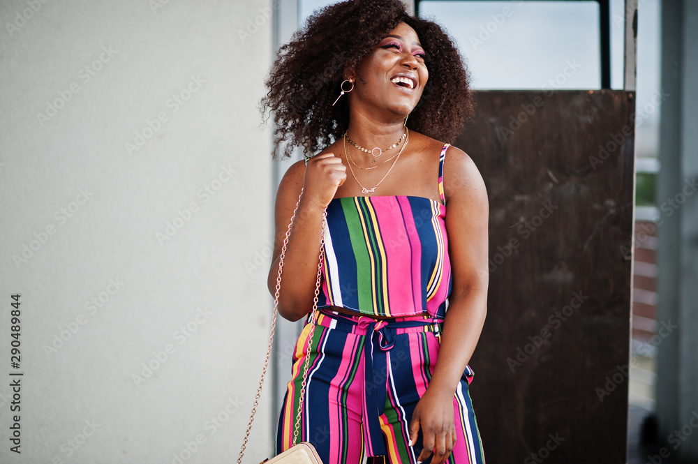 Fototapeta Fashionable african american woman in pink striped jumpsuit, with handbag posed and laughing loudly.
