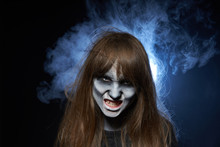 A Girl With Zombie Makeup Over Dark Background With Smoke And Backlight