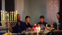 Jewish Family Celebrates Hanukkah By Lighting Menorahs At Sunset