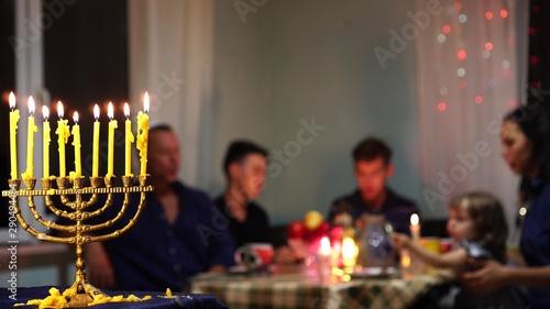 Photo  Jewish family Celebrates Hanukkah by lighting menorahs at sunset