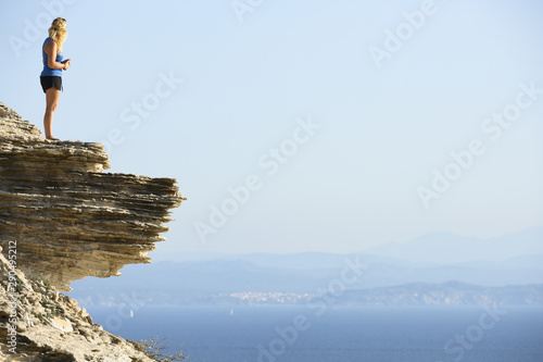 Stunning view of an unidentified blond girl on top of a limestone cliff overlooking the landscape during a beautiful sunset, Bonifacio, Corsica, France Canvas Print