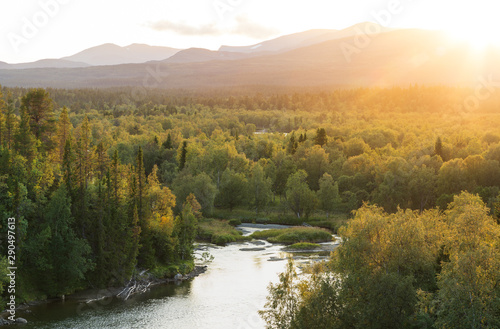 Wall mural - The sun setting over a river in a  forest wilderness. Jamtland, Sweden.