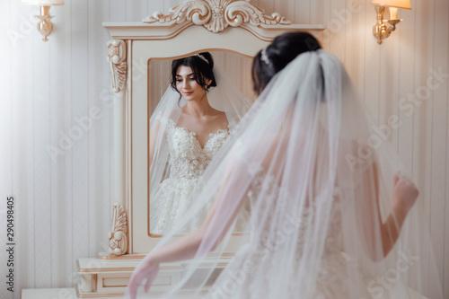 Fotomural Beautiful bride in white dress near a mirror