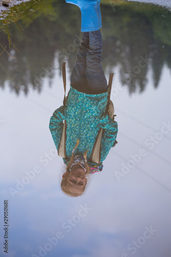 reflection of a little girl in rubber boots in a puddle