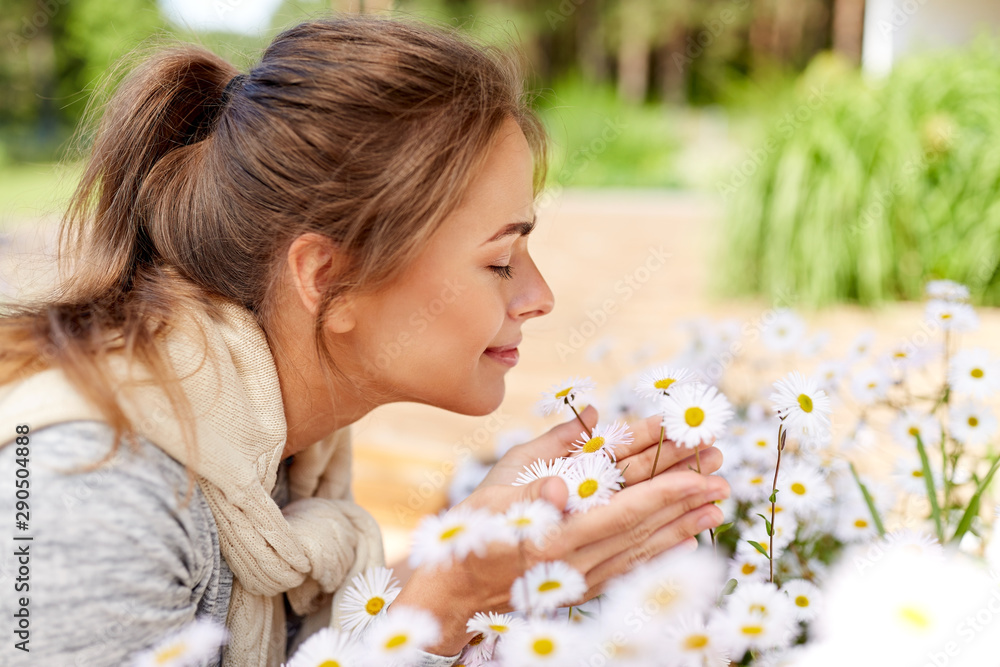 Fototapety, obrazy: gardening and people concept - happy young woman smelling chamomile flowers at summer garden