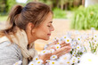 gardening and people concept - happy young woman smelling chamomile flowers at summer garden