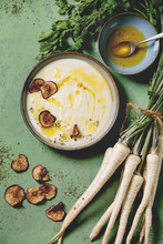 Parsnip Cream Soup In Ceramic Bowl With Sun Dried Pears, Butter Sauce, Bundle Of Fresh Parsnip And Herbs Over Green Texture Background. Flat Lay, Space