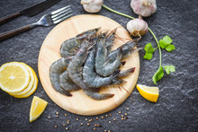 Raw Shrimps On Wooden Cutting Board Plate - Fresh Shrimp Prawns For Cooking With Spices Lemon On Dark Background In The Seafood Restaurant