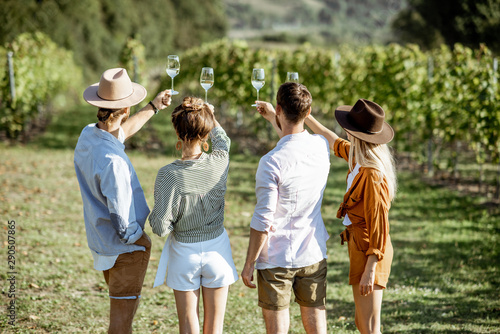 Fotomural Group of young friends tasting wine on the vineyard, looking on the wine glasses
