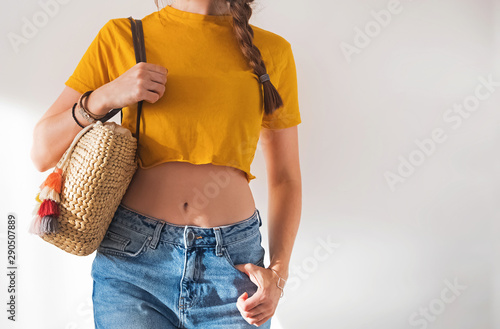 Fotografija Young woman wearing yellow t-shirt and holding straw handbag against white wall