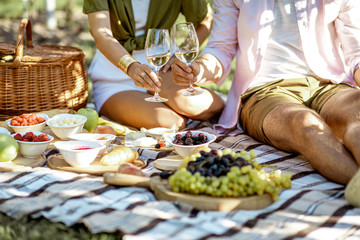 Couple having romantic breakfast outdoors, close-up view on the picnic blanket with lots of tasty food