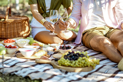 Fototapeta Couple having romantic breakfast outdoors, close-up view on the picnic blanket with lots of tasty food obraz