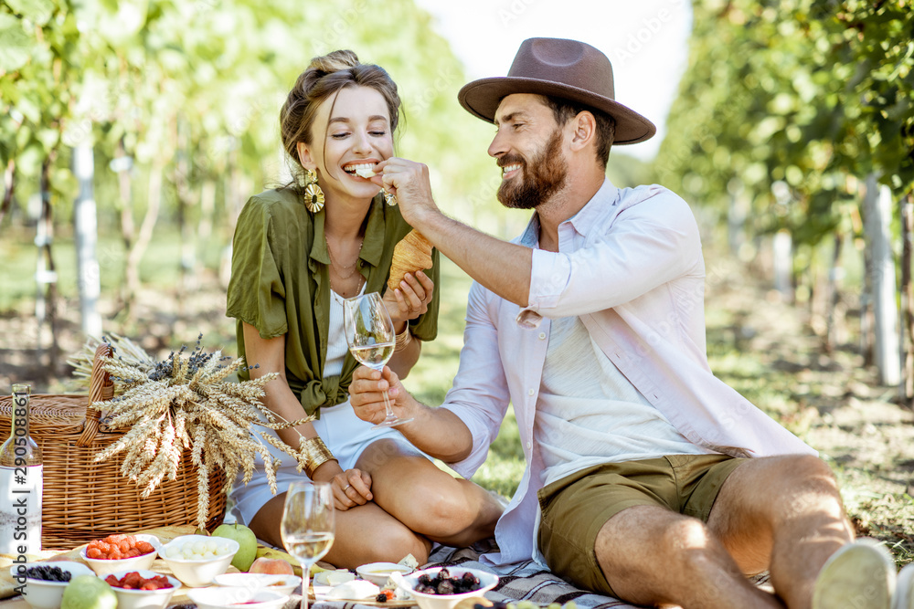 Fototapety, obrazy: Beautiful couple having romantic breakfast with lots of tasty food and wine, sitting together on the picnic blanket at the vineyard on a sunny morning