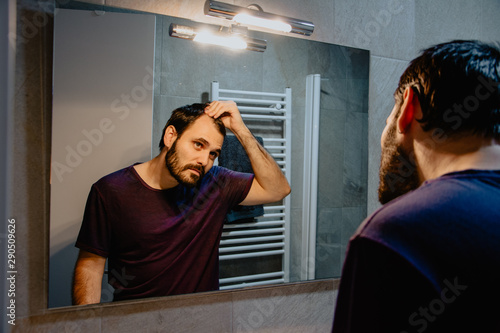 Fototapeta  A worried young white man looks at himself in the mirror and inspects his premature receding hairline