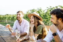 Group Of A Young People Drinking Wine And Talking Together While Sitting At The Dining Table Outdoors On The Vineyard On A Sunny Evening