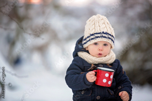 Sweet siblings, children having winter party in snowy forest. Young brothers, boys, drinking tea from thermos. Hot drinks and beverage in cold weather