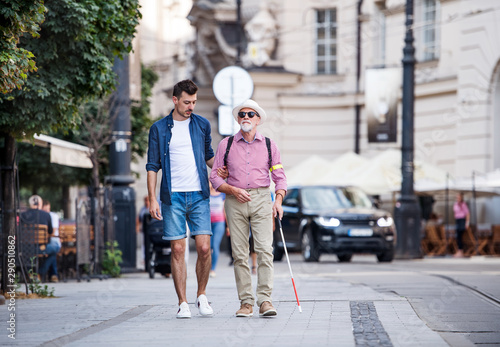Valokuvatapetti Young man and blind senior with white cane walking on pavement in city