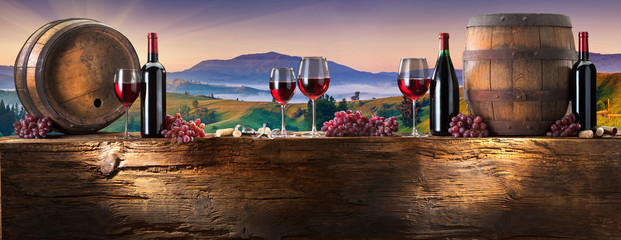 red wine on an old wood with a landscape background