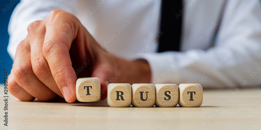 Fototapeta Businessman assembling the word Trust