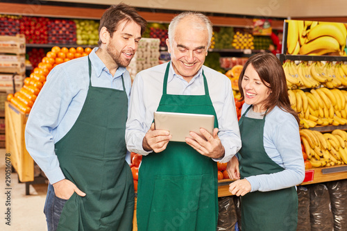 Photographie Marktleiter und Mitarbeiter nutzen Tablet Computer