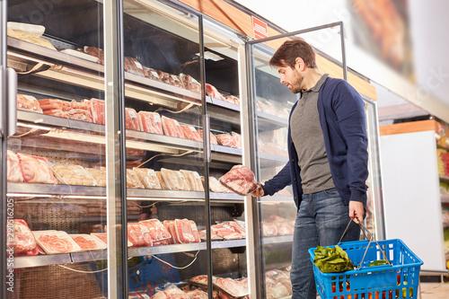 Fotografía Junger Mann am Gefrierschrank beim Fleisch Kauf