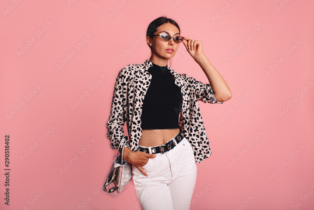 Fototapeta Fashion photo of a beautiful young woman in a casual summer look with animal print shirt, bag and white jeans posing over pink background. Fashion photo, copy space