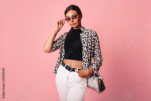 Fototapety, obrazy: Fashion photo of a beautiful young woman in a casual summer look with animal print shirt, bag and white jeans posing over pink background. Fashion photo, copy space