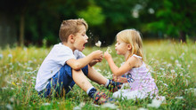 Happy Children Play Outdoor With The Dandelions