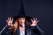 Redhaired Ginger Woman Witch Black Hat And In Leather Jacket Screaming And Scaring With Crazy Make Up On Her Pretty Face In Studio Pink Background