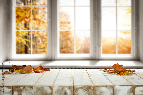 White wooden table and autumn leaves