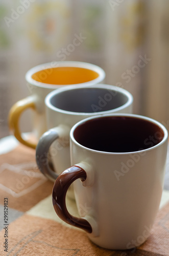 A set of ceramic cups of different colors for three family members. The cups are diagonally aligned. Close-up. Eye level shooting. Soft focus. Portrait orientation. - 290529823