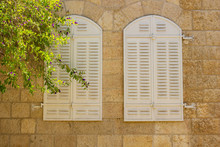 White Arch Closed Window Shutters On Old Stone Wall Medieval European Building Background In Garden Yard With Tree Branch In Picture