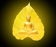 Leinwanddruck Bild Buddha statue  meditation and a bright yellow Bodhi leaf as background Visakha Bucha Day Concept.