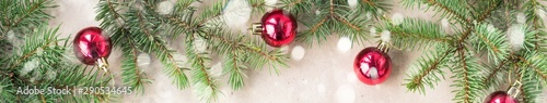 banner of Festive christmas border with red balls on fir branches and snowflakes with snow on rustic beige background