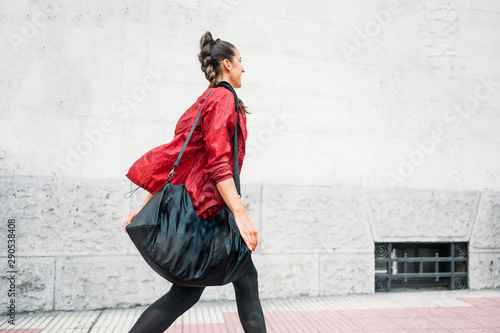 фотографія  Woman looking forward while walking on the way to the gym.