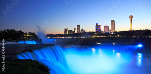 Niagara Falls at dusk including the skyline of the Canadian city of the background