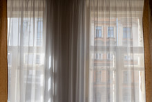 Window View With Tulle And Curtains On The Building Opposite