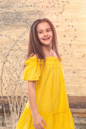 Fotografie, Tablou Portrait of a attractive smiling girl at the fountain