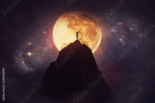 Fotografía Self overcome concept as a person raising hands up on the top of a mountain over full moon night background