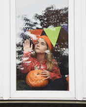 Child Holding Pumpkin Looking Outside Window