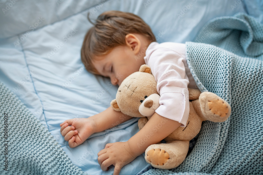 Fototapety, obrazy: Sleepyhead. Young boy peacefully sleeping on a blue pillow. Baby needs his sleep! Baby boy sleeping with teddy bear and pacifier. Baby sleeping covered with soft blanket