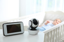Baby Monitor And Camera On Table Near Crib With Child In Room. Video Nanny