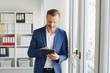 Stylish businessman using a handheld tablet-pc