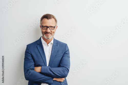 Friendly businessman posing with folded arms