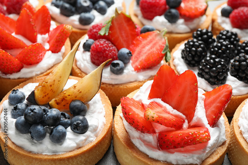 Fototapeta Many different berry tarts on table, closeup. Delicious pastries