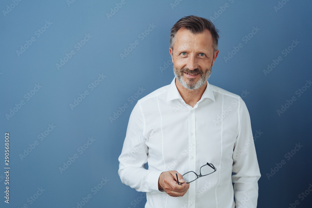 Fototapeta Friendly relaxed middle-aged man holding glasses