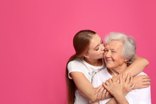 Young Woman Kissing Her Grandmother On Pink Background. Space For Text