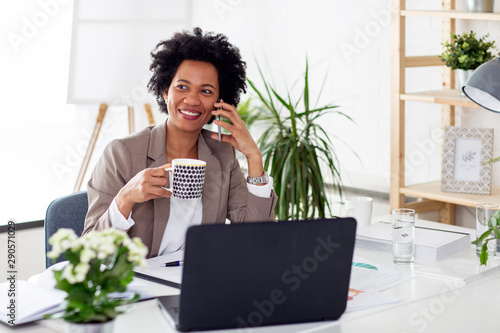 Foto  Woman using mobile phone while sitting at the desk in office with laptop in fron