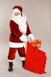 Authentic Santa Claus with sack and gift on grey background