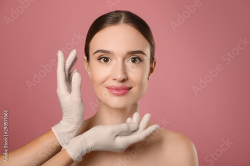 Valokuva  Doctor examining woman's face before plastic surgery on pink background
